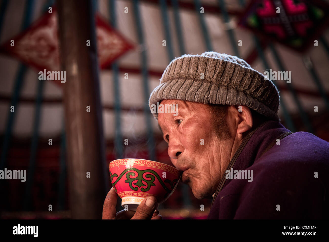 Rural old man Mongolian Kazakh eagle hunter sipping drinking tea inside ger - Stock Image