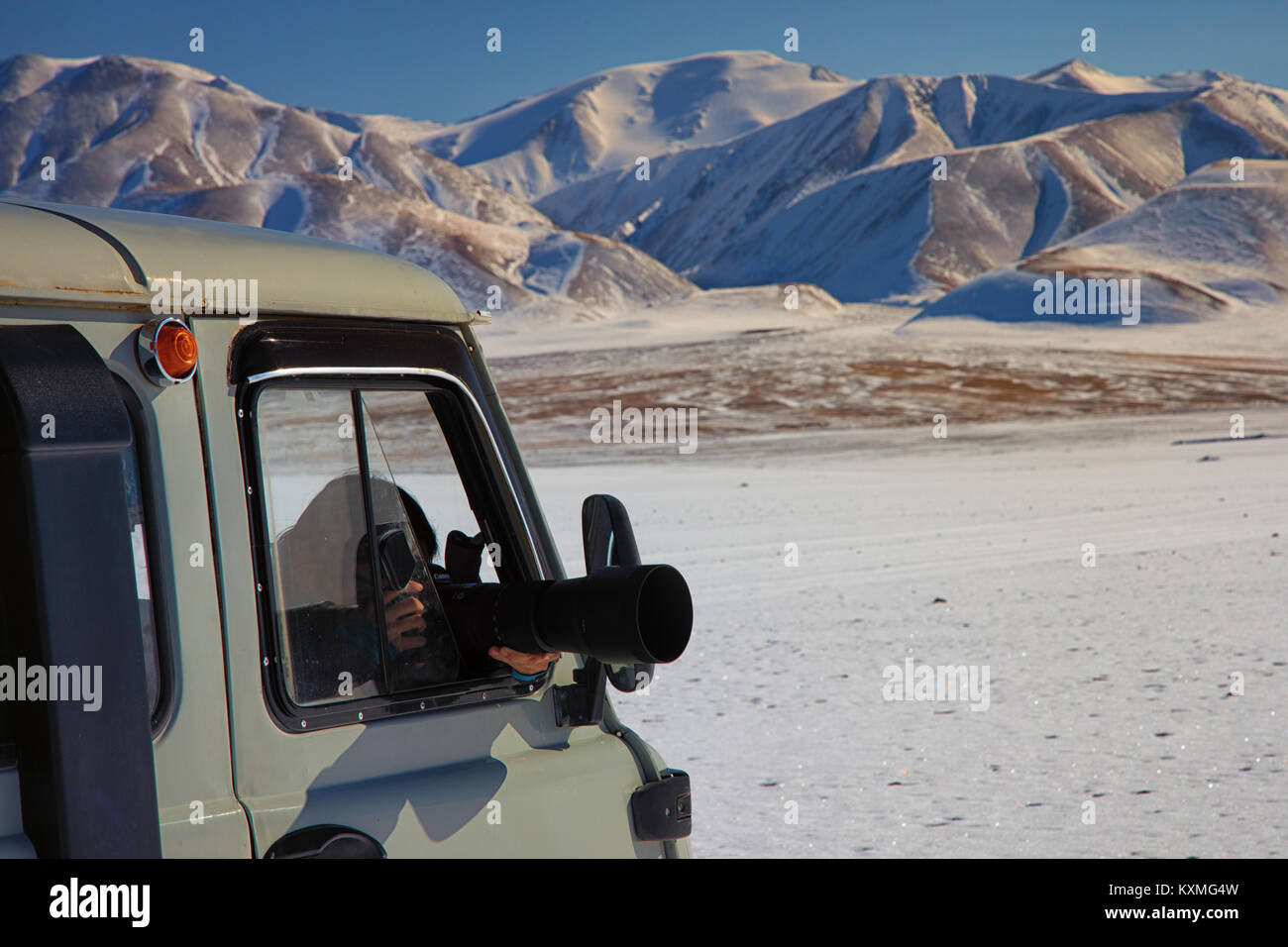 Girl taking pictures russian van UAZ 452 camper dslr zoom lengs sigma 150-600mm snow winter Mongolia snowy mountains - Stock Image