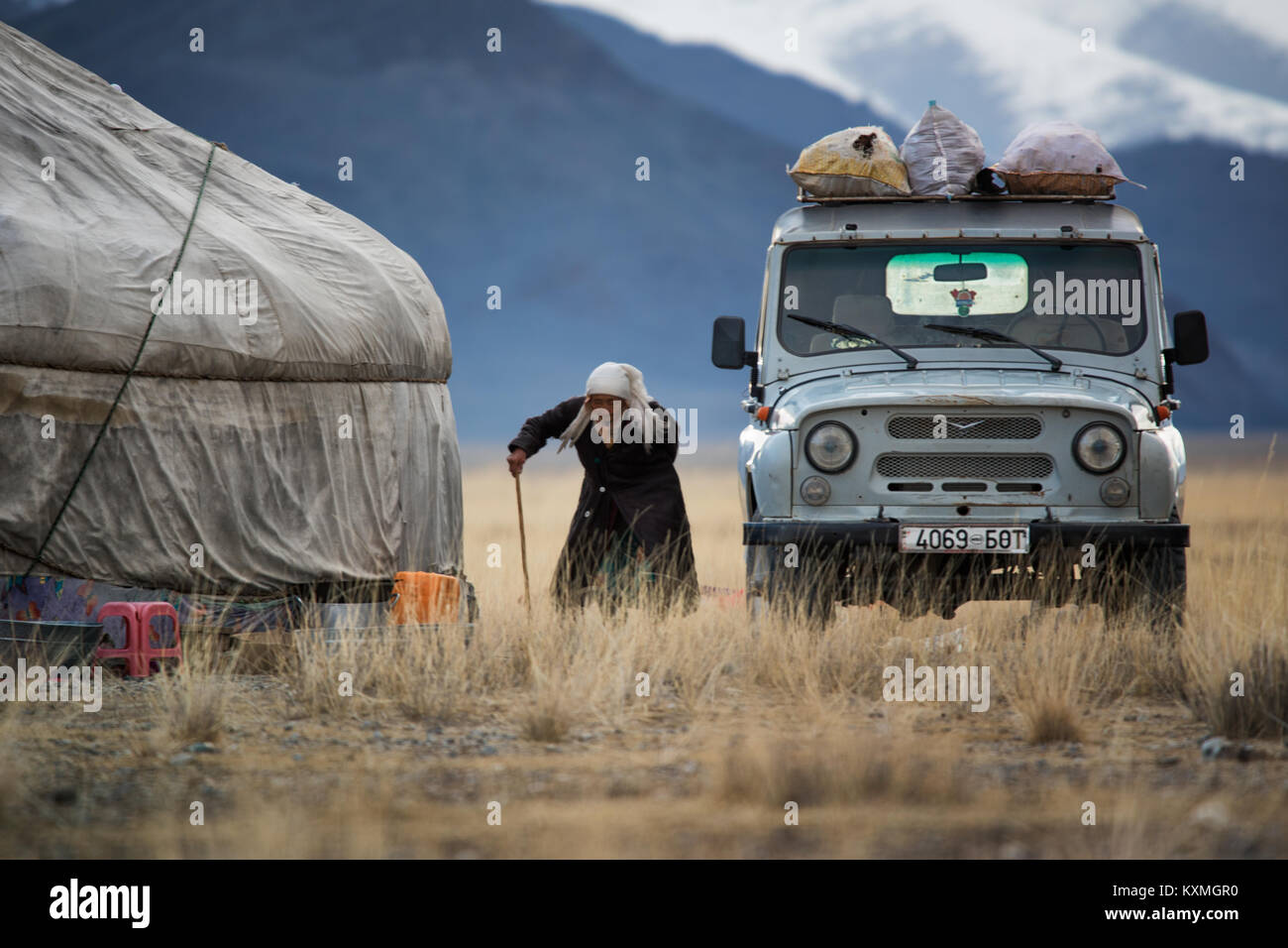 Old woman goat shepherd  returning home ger winter Mongolia steppes grasslands offroad 4x4 - Stock Image