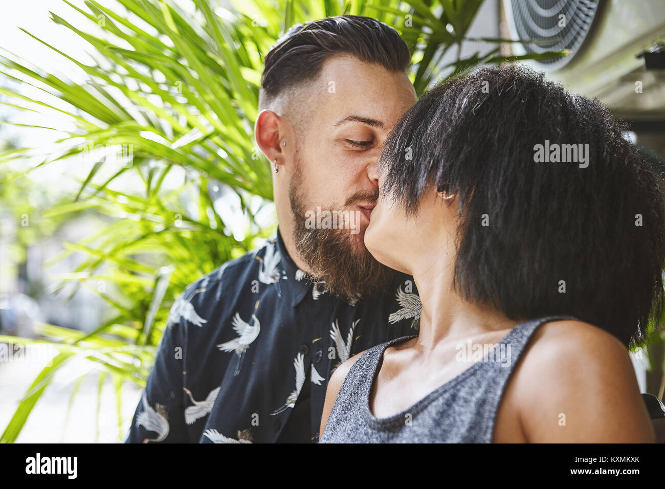 Multi ethnic couple kissing in residential alleyway,Shanghai French Concession,Shanghai,China - Stock Image