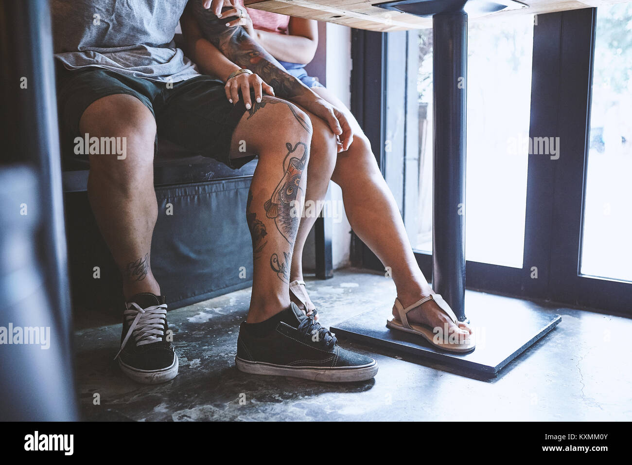 Waist down of multi ethnic hipster couple in cafe with hand on each others knee,Shanghai French Concession,Shanghai,China - Stock Image