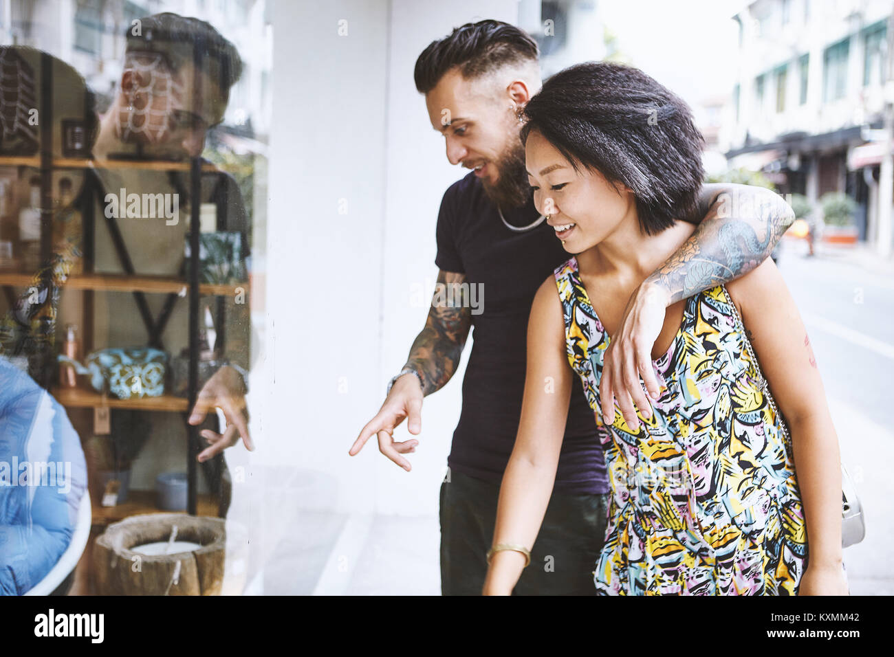 Multi ethnic hipster couple looking and pointing at shop window,Shanghai French Concession,Shanghai,China - Stock Image