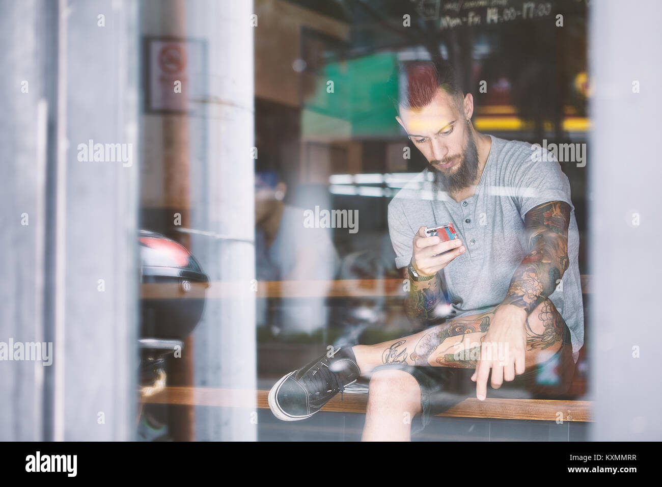 Young male hipster in cafe window seat looking at smartphone,Shanghai French Concession,Shanghai,China - Stock Image