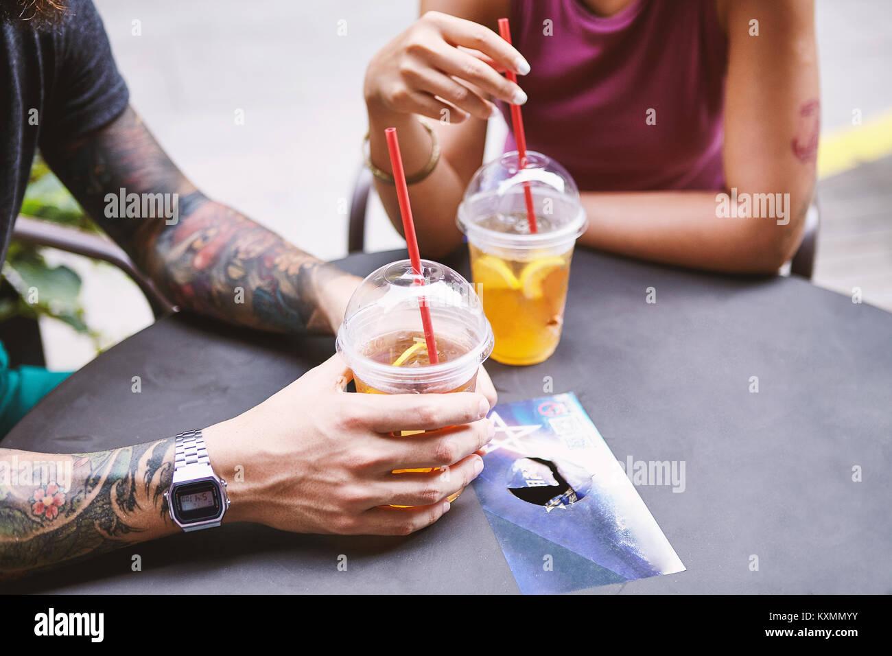 Cropped shot of multi ethnic hipster couple at sidewalk cafe,Shanghai French Concession,Shanghai,China - Stock Image