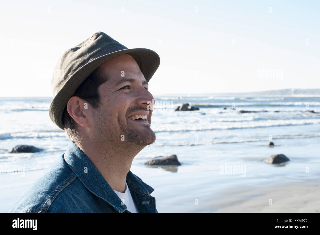 Happy mid adult man in trilby on beach,Cape Town,Western Cape,South Africa - Stock Image