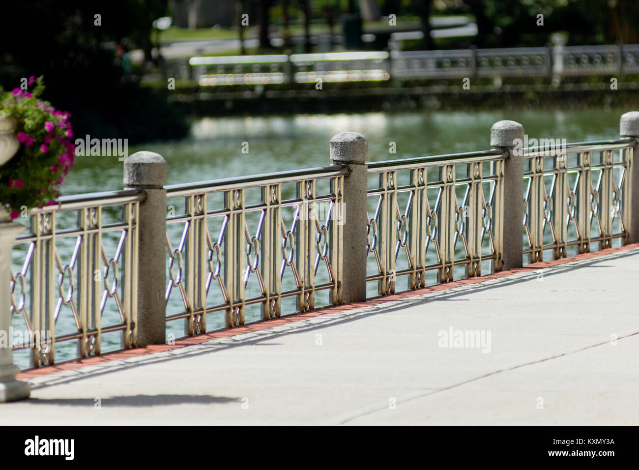Public park Polished metal banister railings barrier to lake edge on sunny day. - Stock Image
