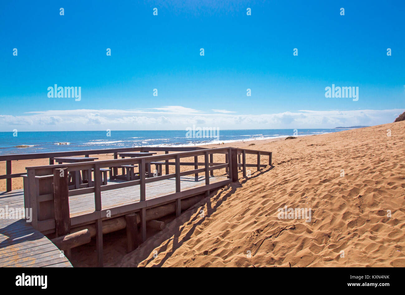 Empty wooden walkway entrance onto sandy beach against sea and blue cloudy sky landscape at Mtunzini in South Africa - Stock Image
