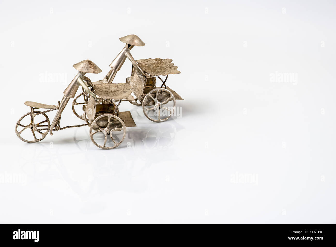 Far eastern three wheel bicycle figurines isolated on white background made of metal - Stock Image