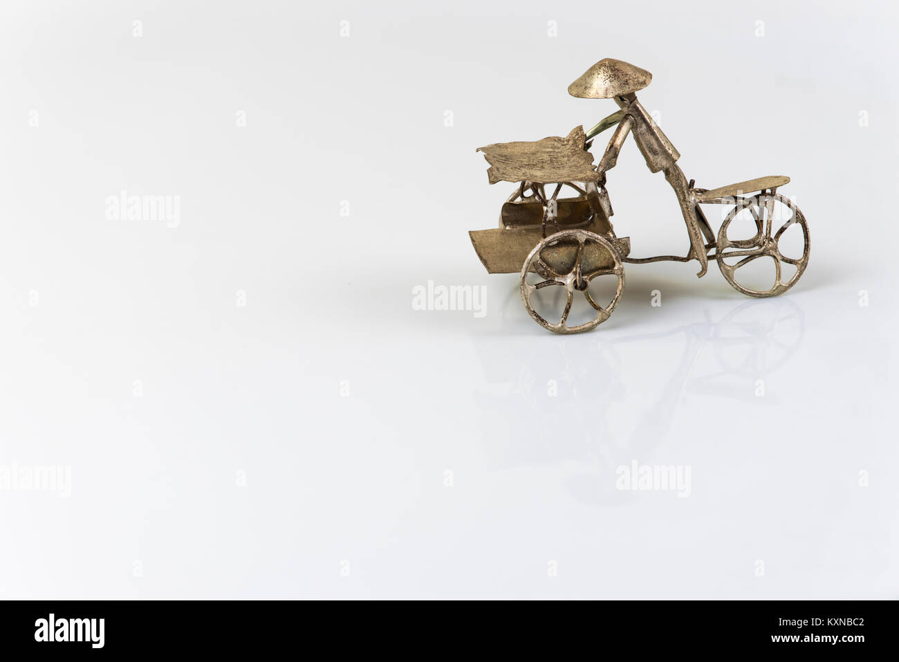Far eastern three wheel bicycle figurine isolated on white background made of metal - Stock Image