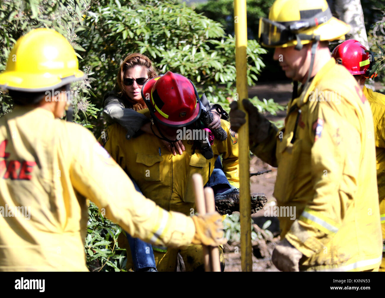 Montecito, California, USA. 10th Jan, 2018. Cal Fire carries a woman through mud and debris along Olive Mill Rd - Stock Image