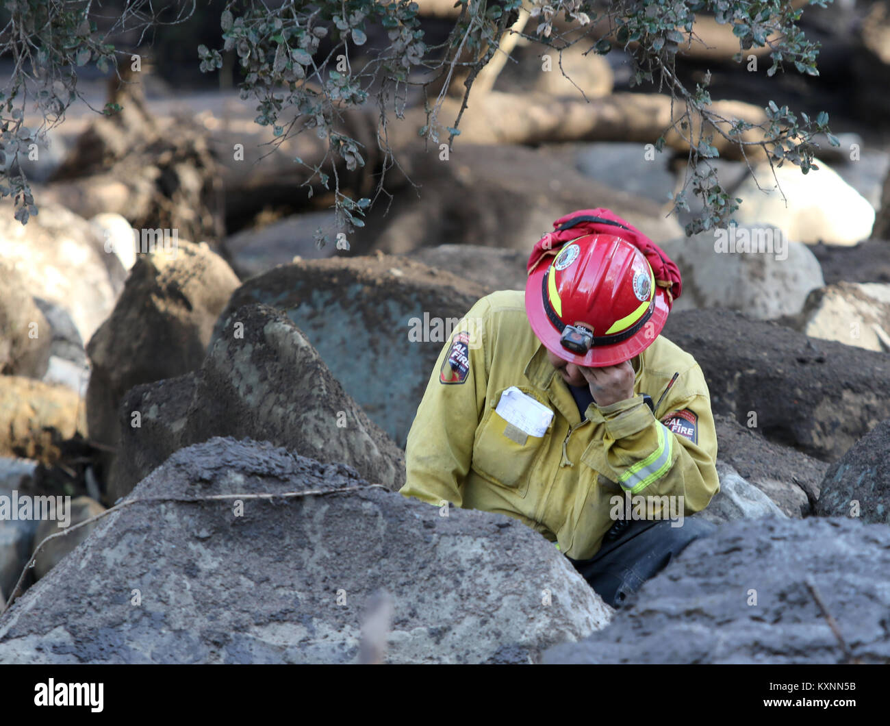 Montecito, California, USA. 10th Jan, 2018. A Cal Fire Firefighter rests his head after digging for a body along - Stock Image