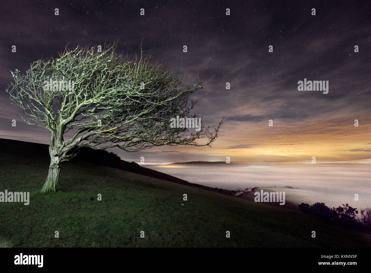 Firle, UK. 10th Jan, 2018. A colourful moonrise at midnight illuminates freezing fog below the Soth Downs National - Stock Image