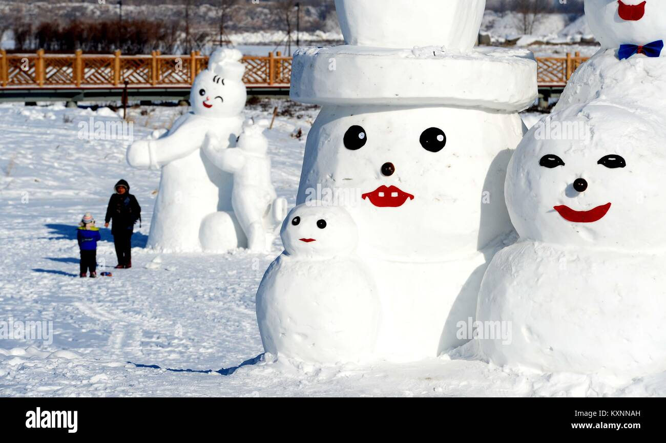 Harbin, China's Heilongjiang Province. 11th Jan, 2018. People watch snowman sculptures at an ice and snow park in Stock Photo
