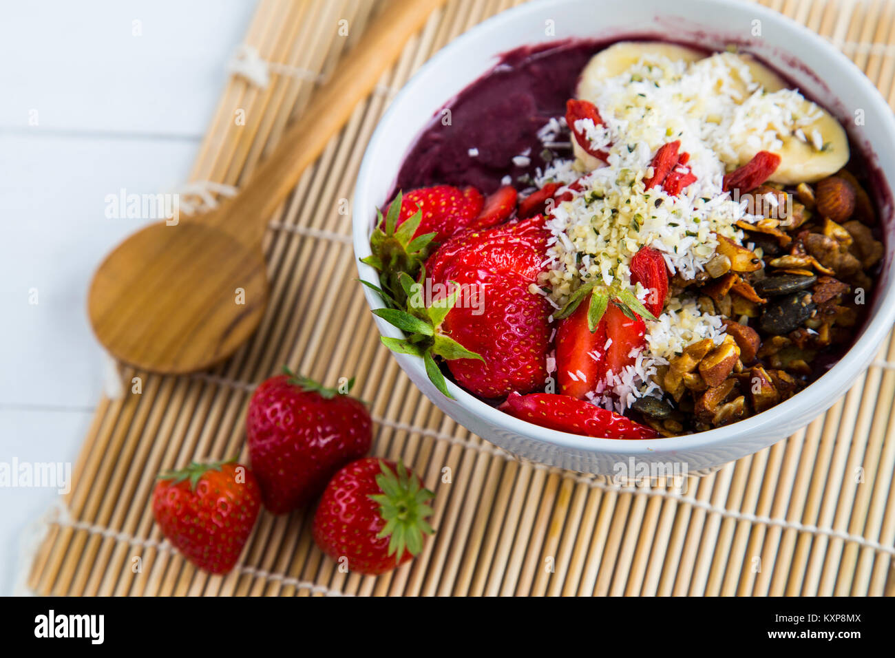 Acai bowl and strawberries - Bowl of acai purée with toppings of banana, strawberry, granola and seeds. - Stock Image