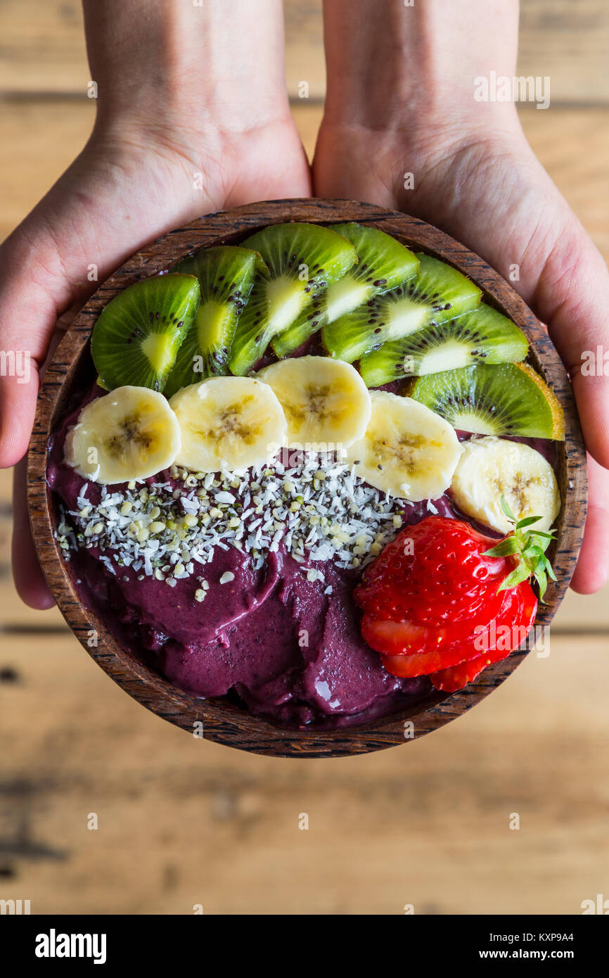 Acai bowl in hands - Bowl of acai purée with toppings of banana, kiwi, strawberry and seeds. - Stock Image