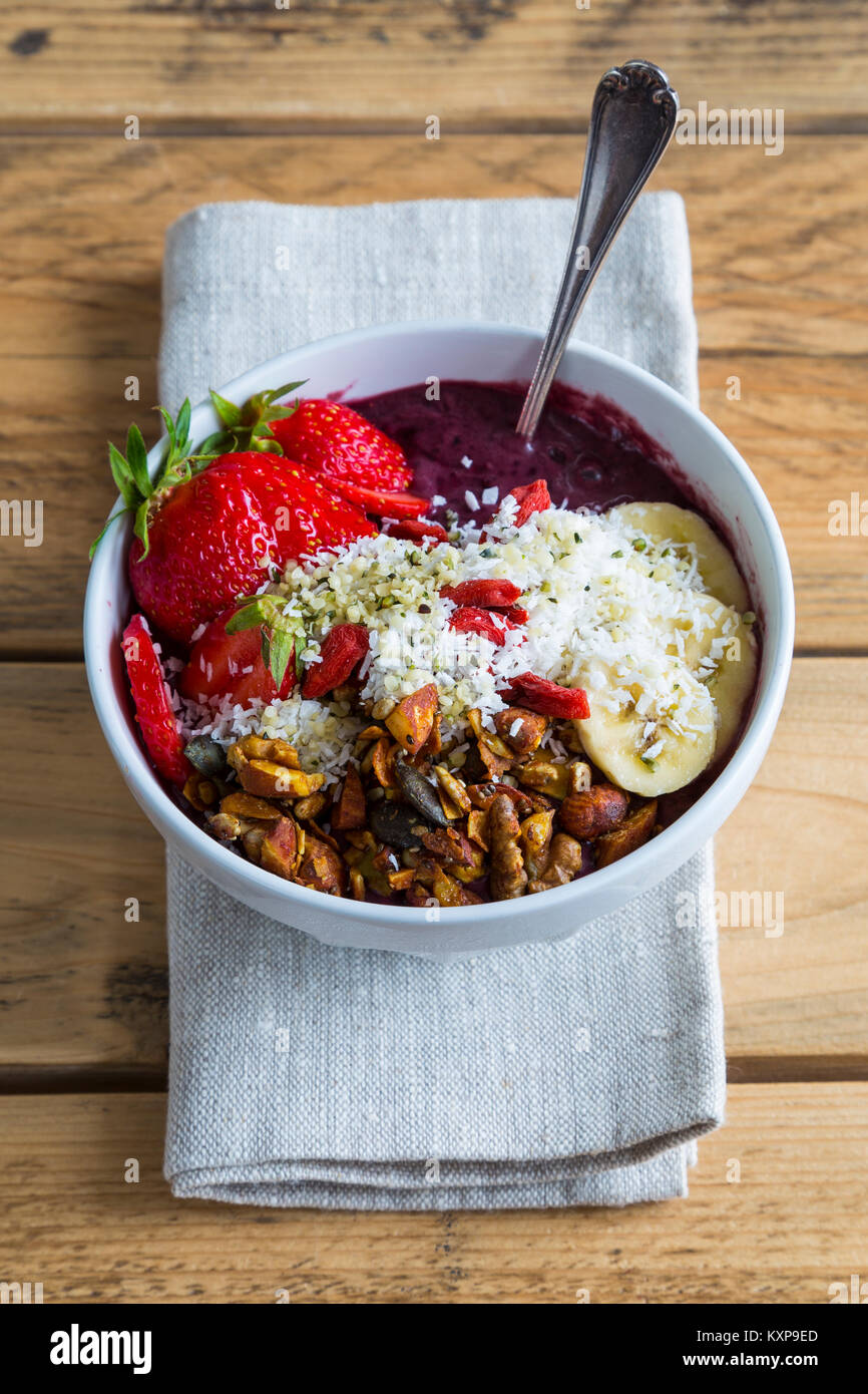 Acai bowl on napkin - Bowl of acai purée with toppings of banana, strawberry, granola and seeds. - Stock Image