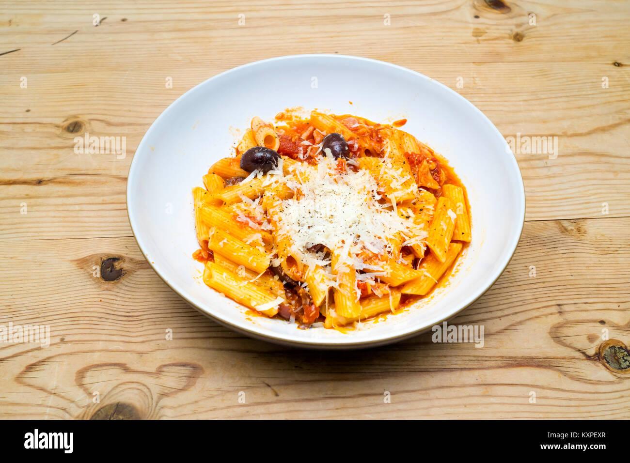 Food Penne Pasta Tonno made with tuna, bacon, tomatoes and Basil, Kalamata Olives, and Pecorino Romano grated cheese - Stock Image