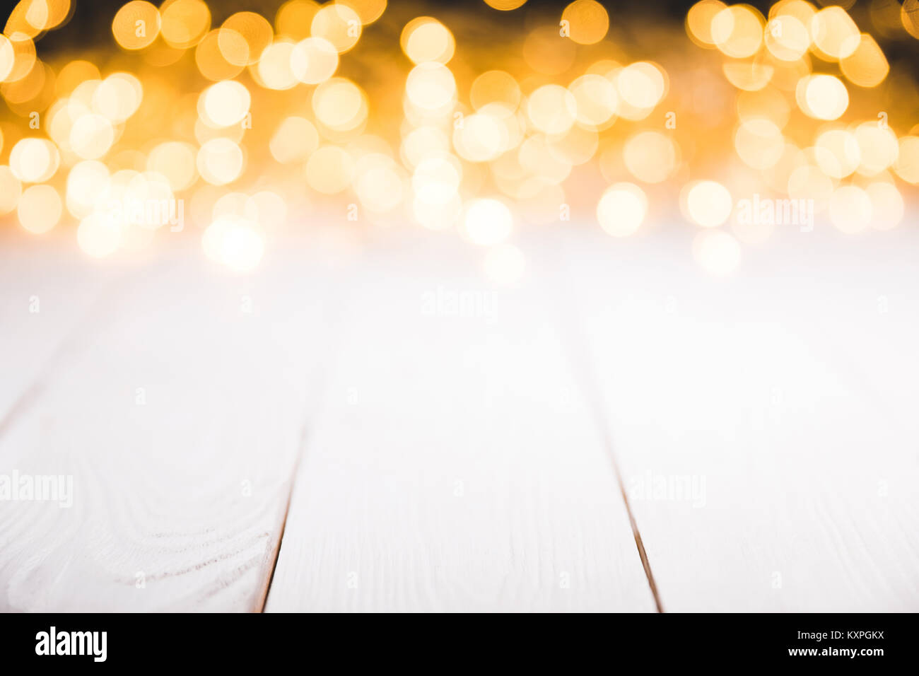 magical blurred lights on white wooden surface, christmas texture - Stock Image