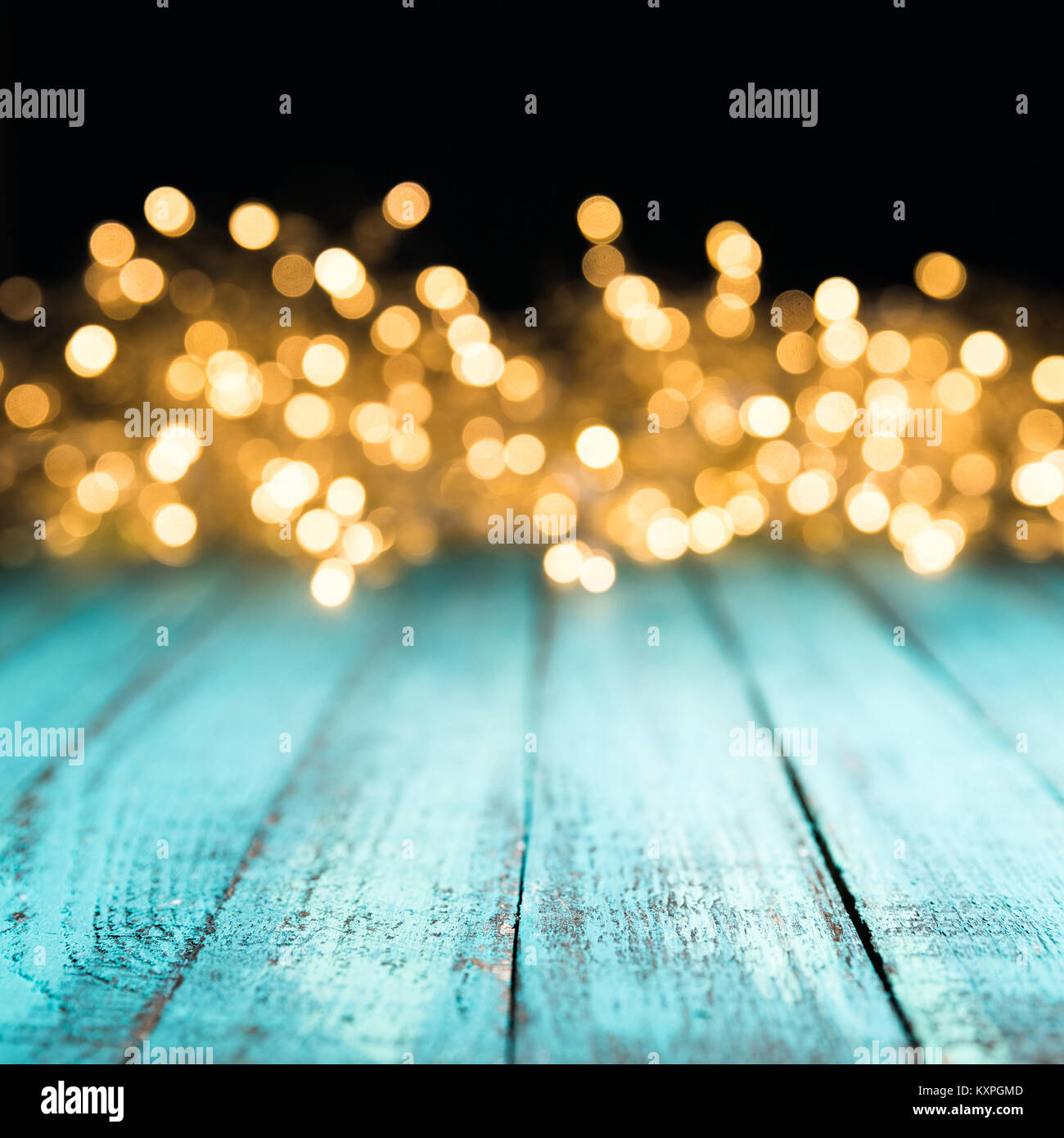 decorative bokeh lights on blue wooden surface, christmas background - Stock Image