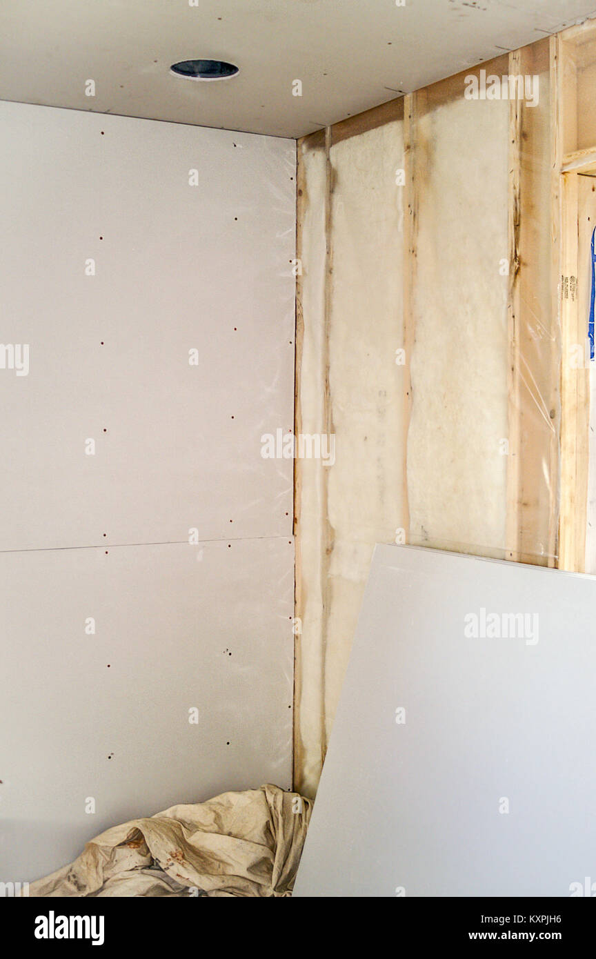 From studs to insulation to sheetrock plus an opening for a recessed light - Stock Image