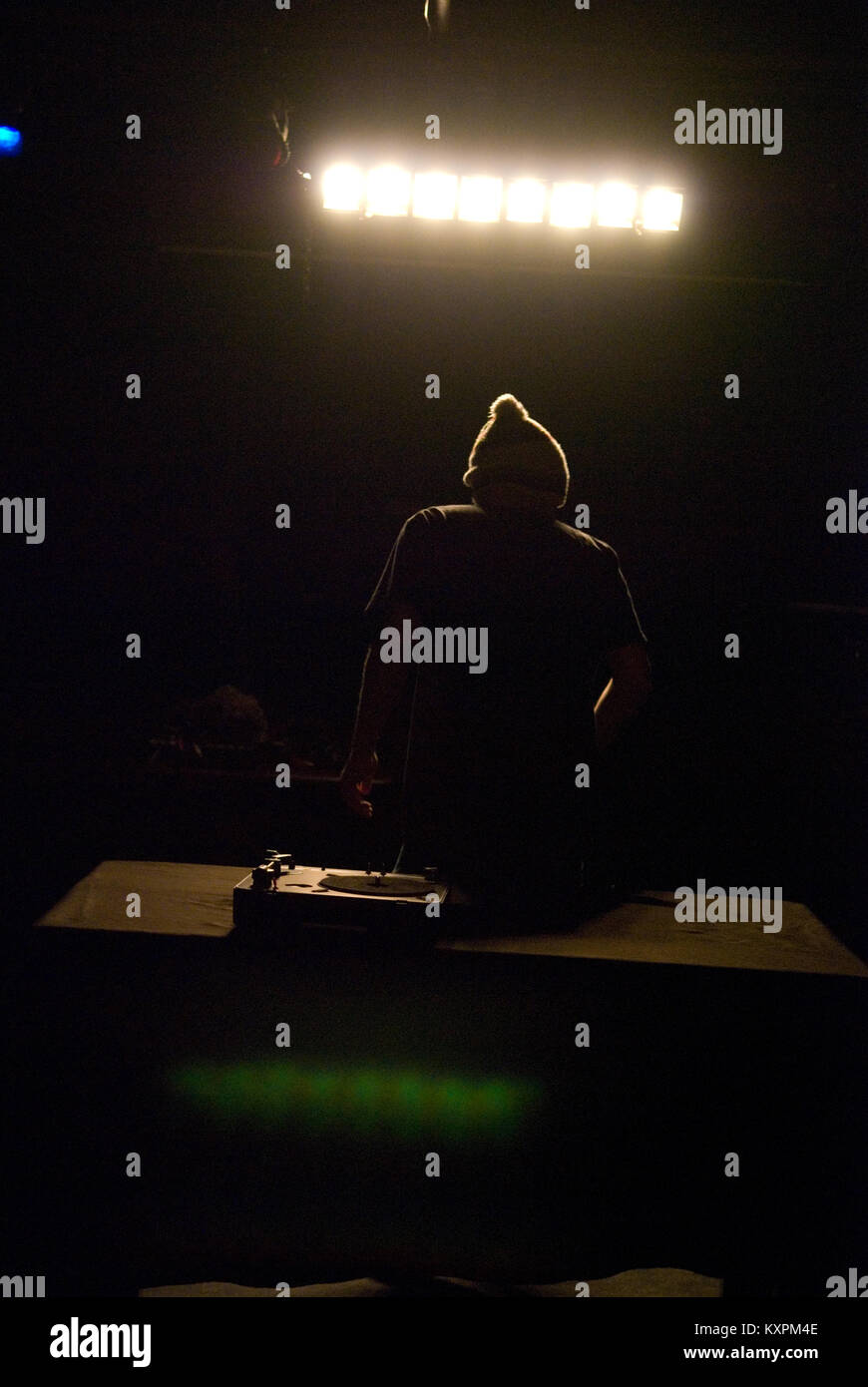 a DJ with a woolly hat selects vinyl records to play on his tunrtable in this low light club scene - Stock Image