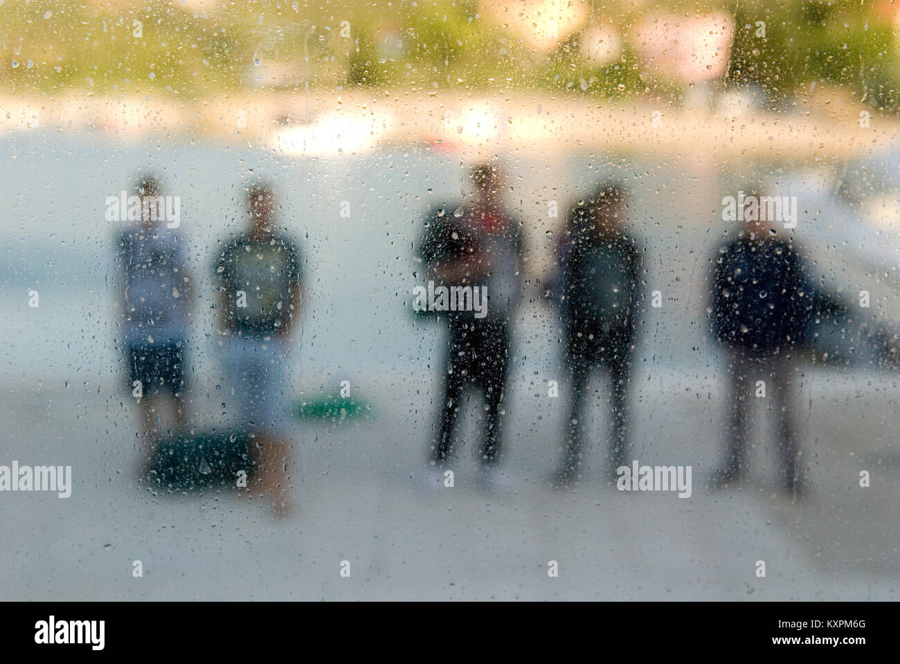 looking through a window covered in water droplets and condensation at a group fo five people standing with their - Stock Image
