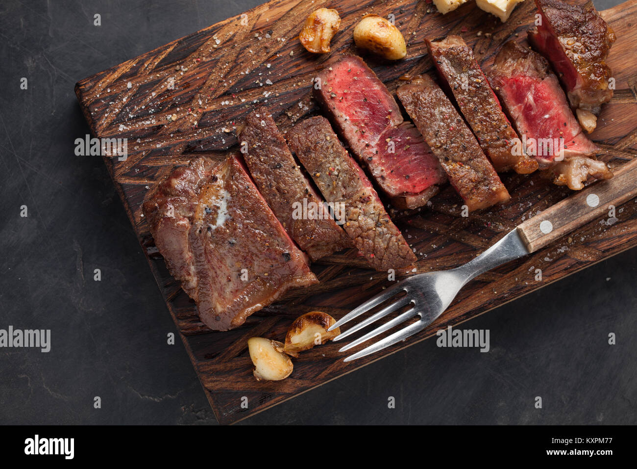 Closeup ready to eat steak new York beef breeds of black Angus with herbs, garlic and butter on a wooden Board. - Stock Image
