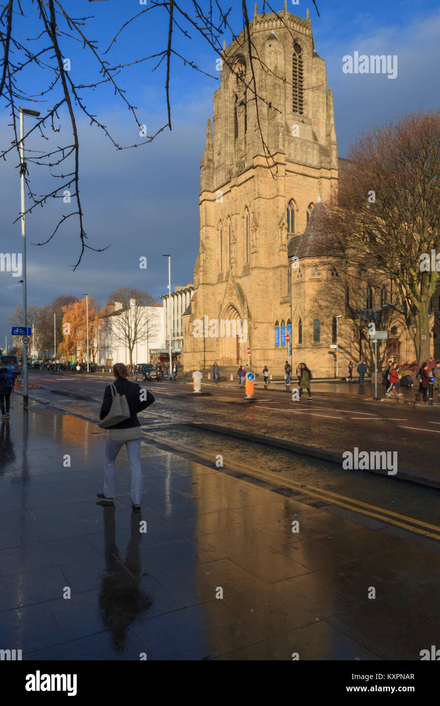 The Holy Name Church, reflected in the wet pavement, Oxford Road, Manchester, UK - Stock Image