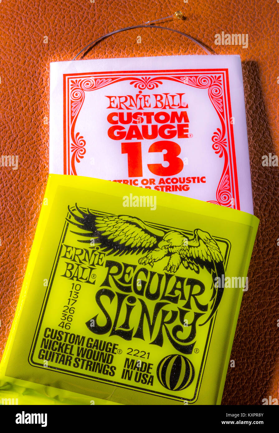 A set of Ernie Ball, regular slinky gauge, electric guitar strings, with one unwound string protruding from its - Stock Image