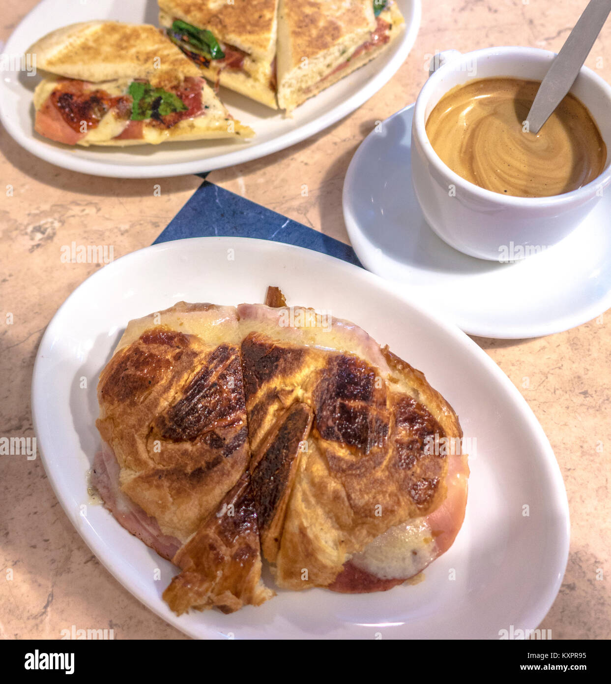 Italian cafe in London. Lunchtime food and drink. Cup of espresso coffee alongside a meal of ham and brie panini - Stock Image