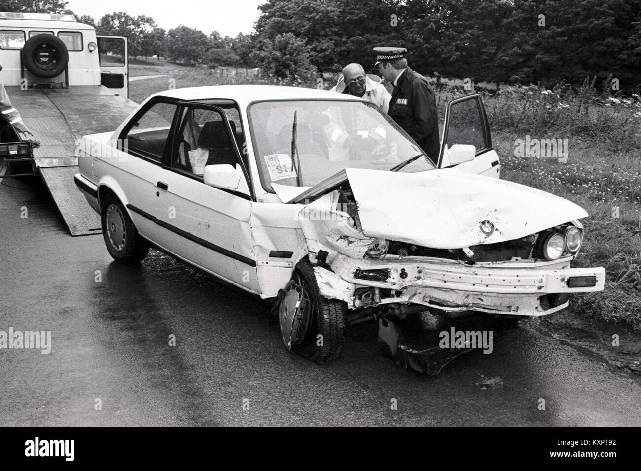 a crashed white 1988 bmw 3 series is prepared for towing following