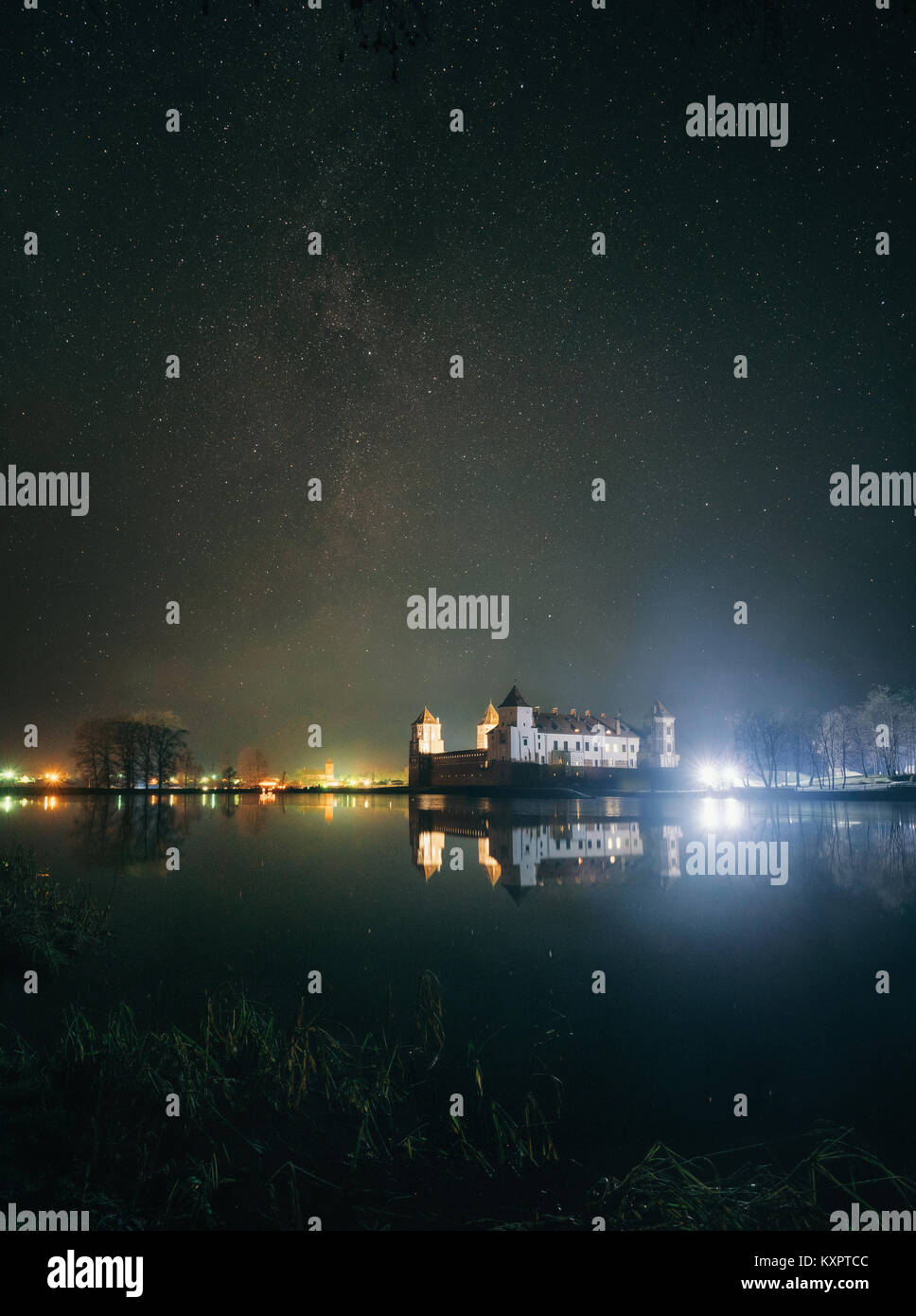 Scenic view of Mir Castle Complex in night with starry sky and glow reflexion on lake. Landmark in Belarus - Stock Image