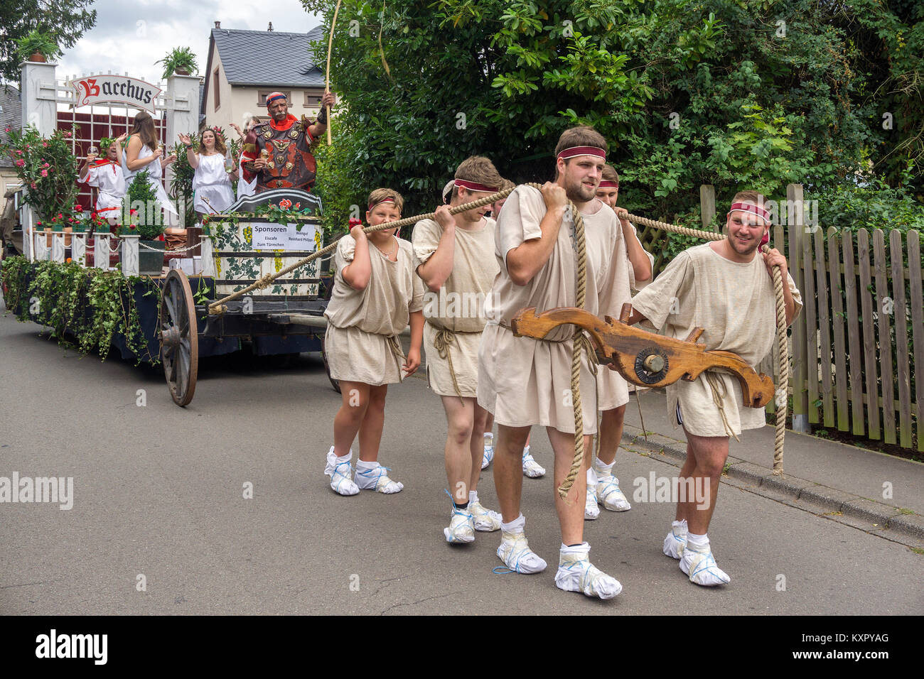 Locals with roman slave costumes pulling a float with wine queen and god of wine Bacchuss, wineship festival, Neumagen Stock Photo