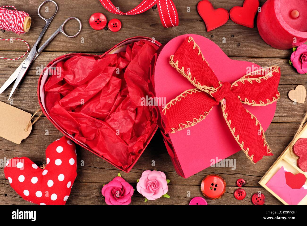 Open, empty Valentines Day heart shaped gift box with decor and crafting frame against a rustic wood background - Stock Image