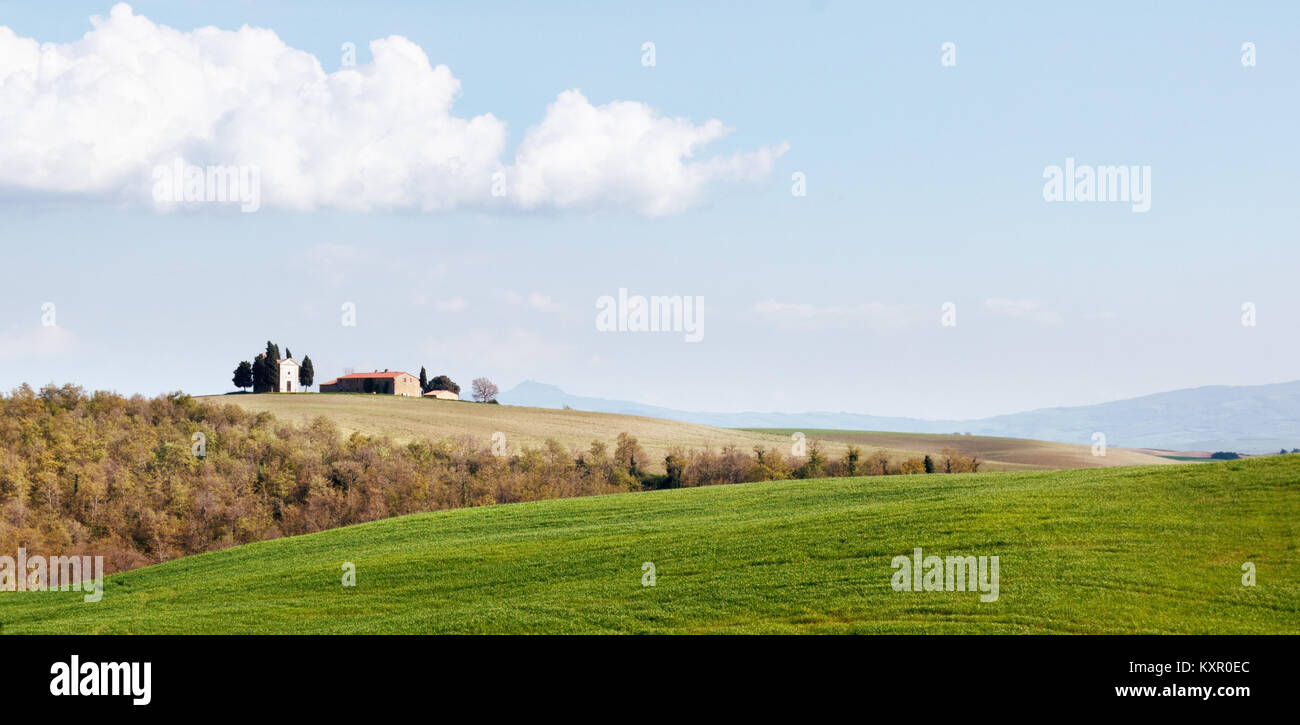 TUSCANY, ITALY - APRIL 14, 2014: Hilly Tuscan plowed farm lands on a sunny day in spring with a barn and a chapel - Stock Image