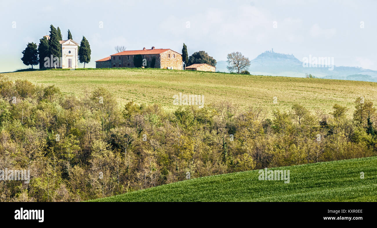 TUSCANY, ITALY - APRIL 14, 2014: Plowed farm lands in Tuscany on a sunny day in spring with a barn and a chapel - Stock Image