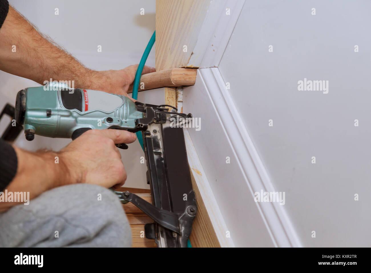 Carpenter brad using nail gun to Moulding trim, with the warning ...