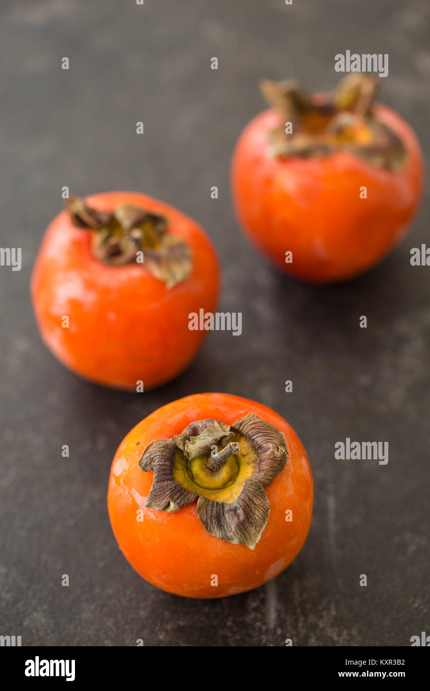 Three persimmons on black rustic tabletop with one persimmon in sharp focus and others blurred. Vertical composition. - Stock Image
