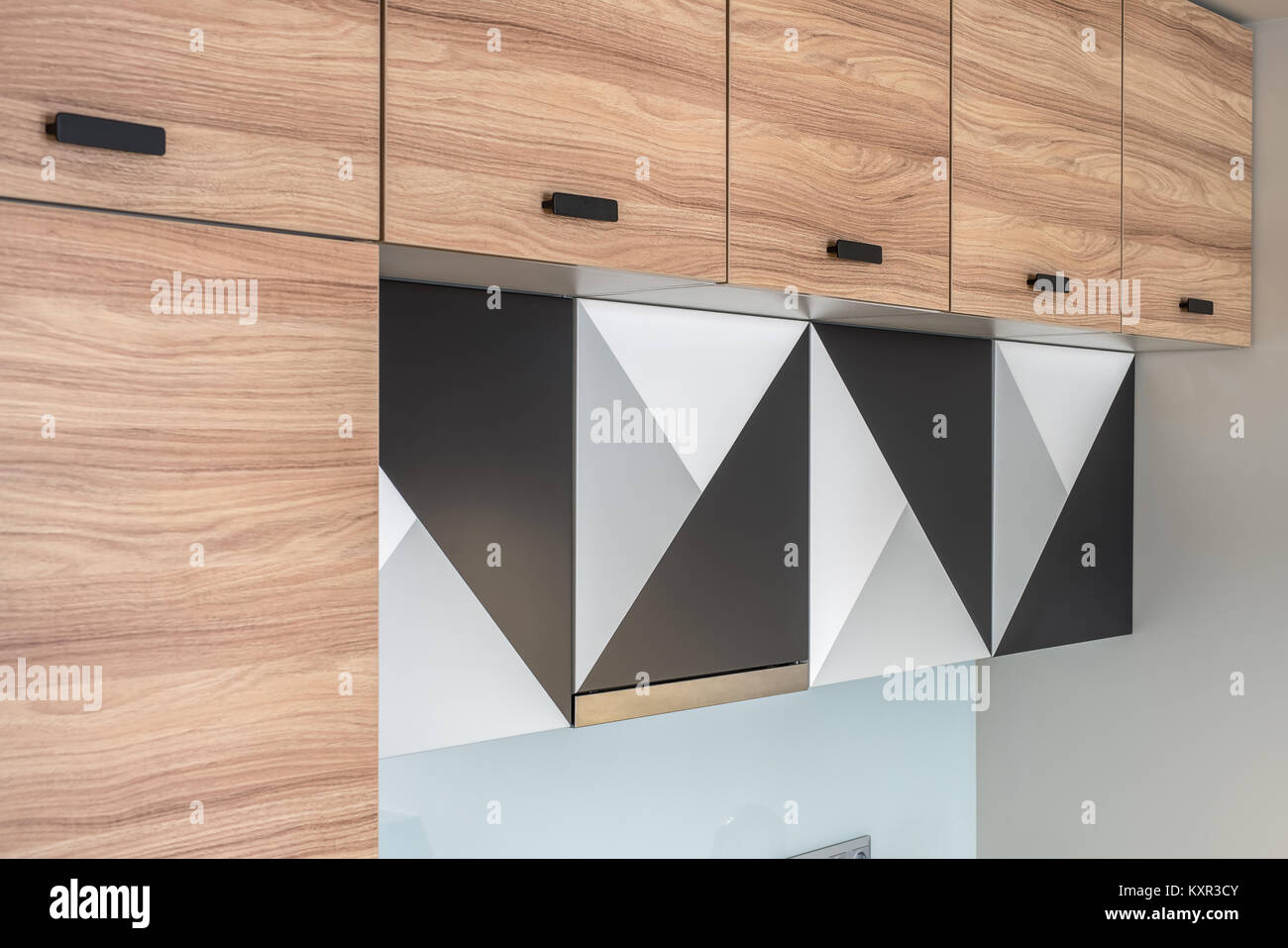 Wooden lockers with black handles on the modern kitchen ...