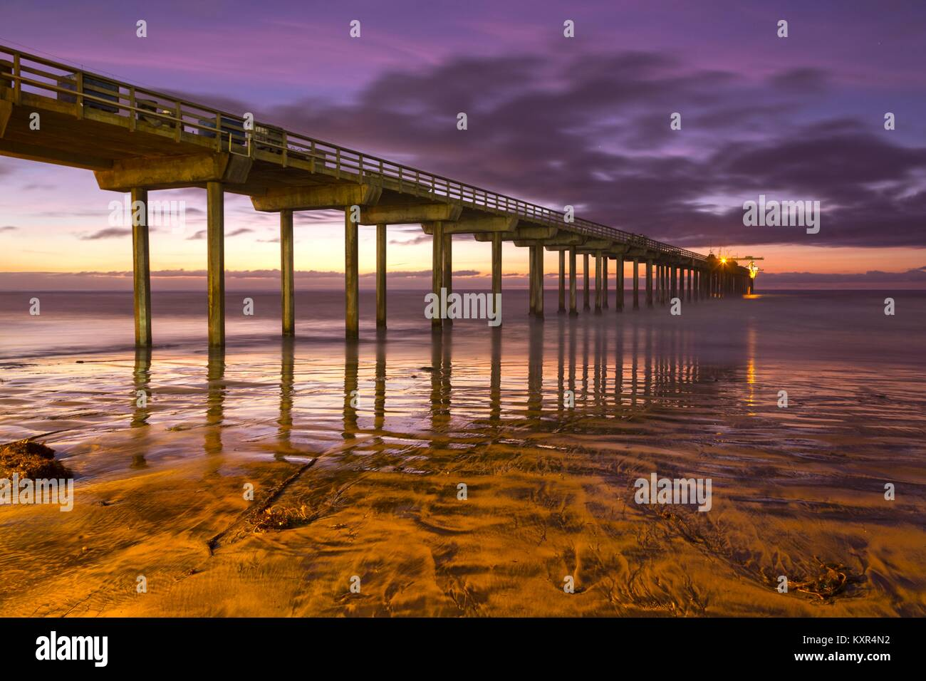 Scripps Pier Sunset Colors and La Jolla Shores Beach with distant Pacific Ocean on the Horizon north of San Diego - Stock Image
