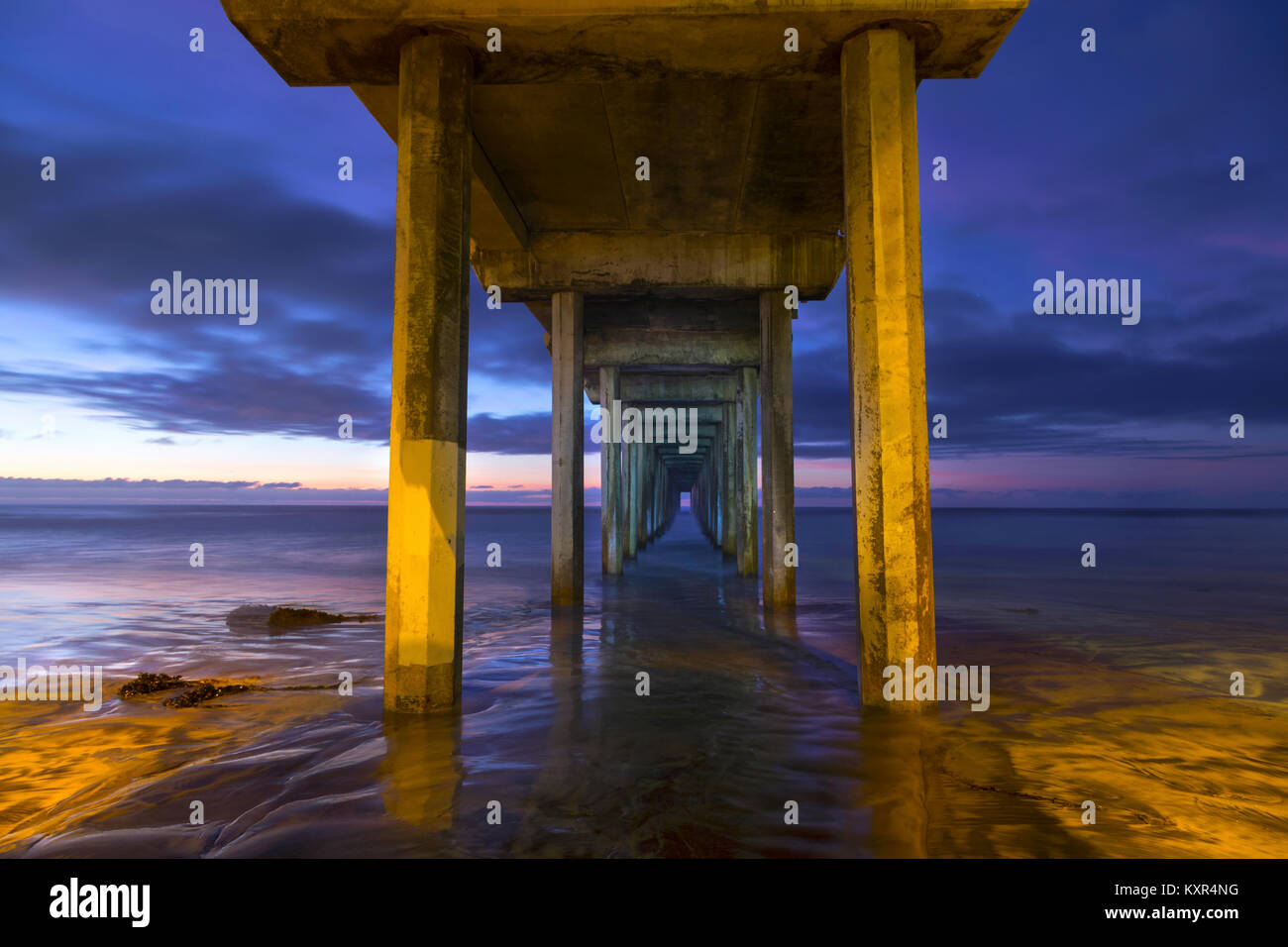 Symmetrical Pattern of Scripps Pier and Dramatic Sunset Sky Colors below UCSD Institute of Oceanography, La Jolla - Stock Image