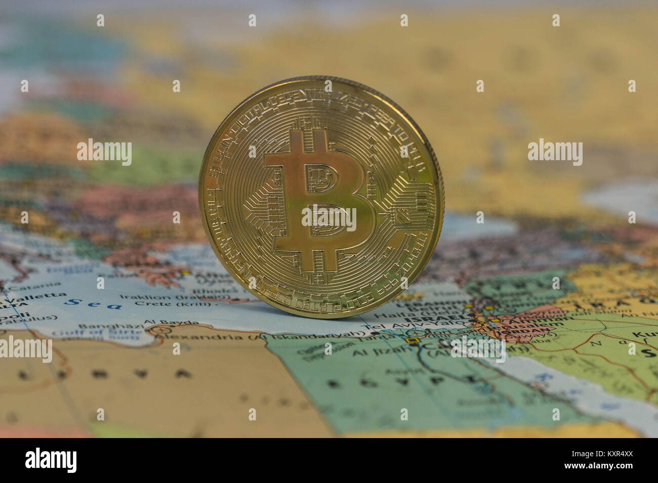 Golden Bitcoin Coin close up with blurred background of the Middle East. - Stock Image