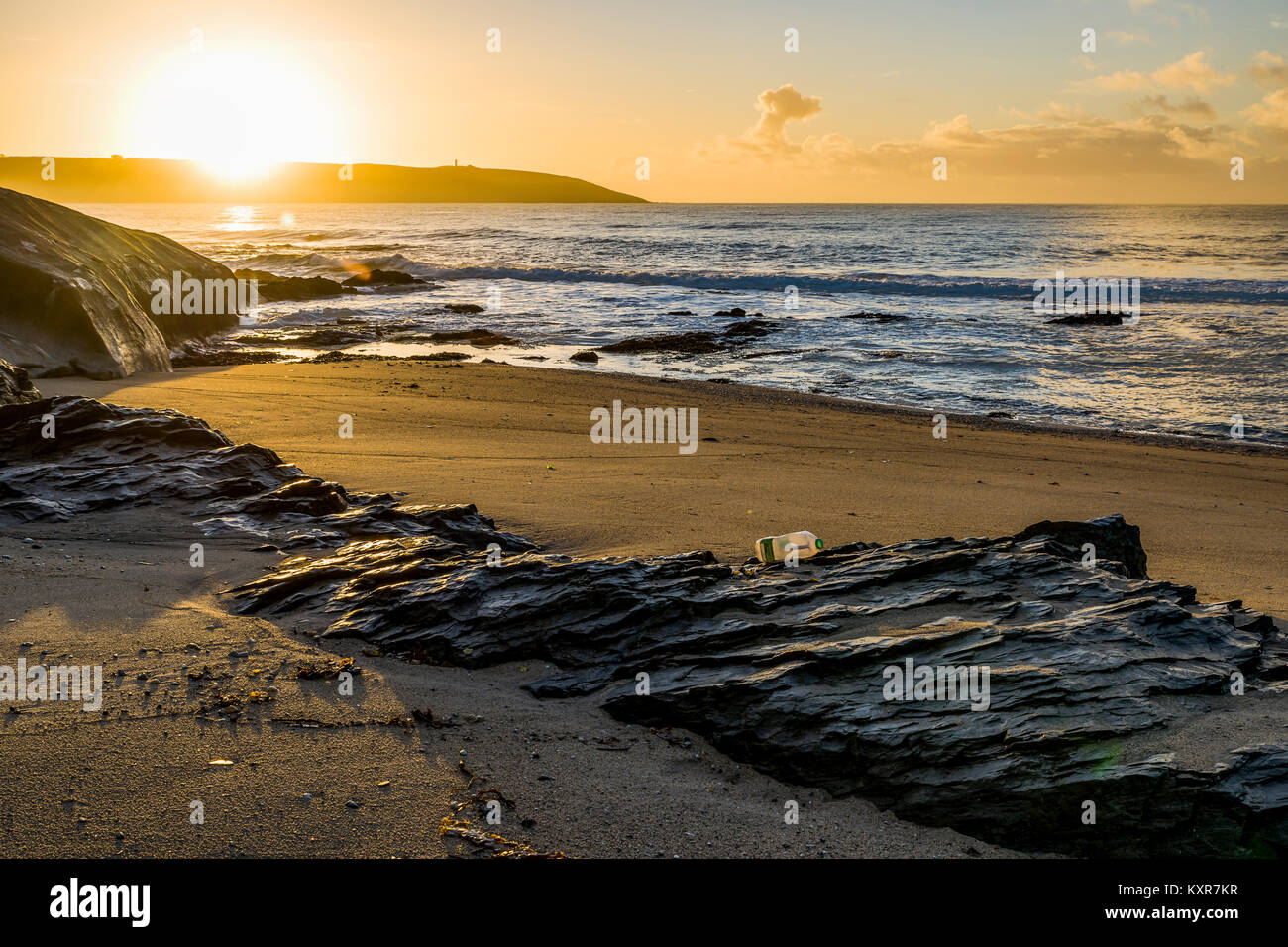 Spit Beach, St Austell Bay, Cornwall, UK. 10/01/2018, sunrise and shortly after. A discarded milk bottle faintly - Stock Image