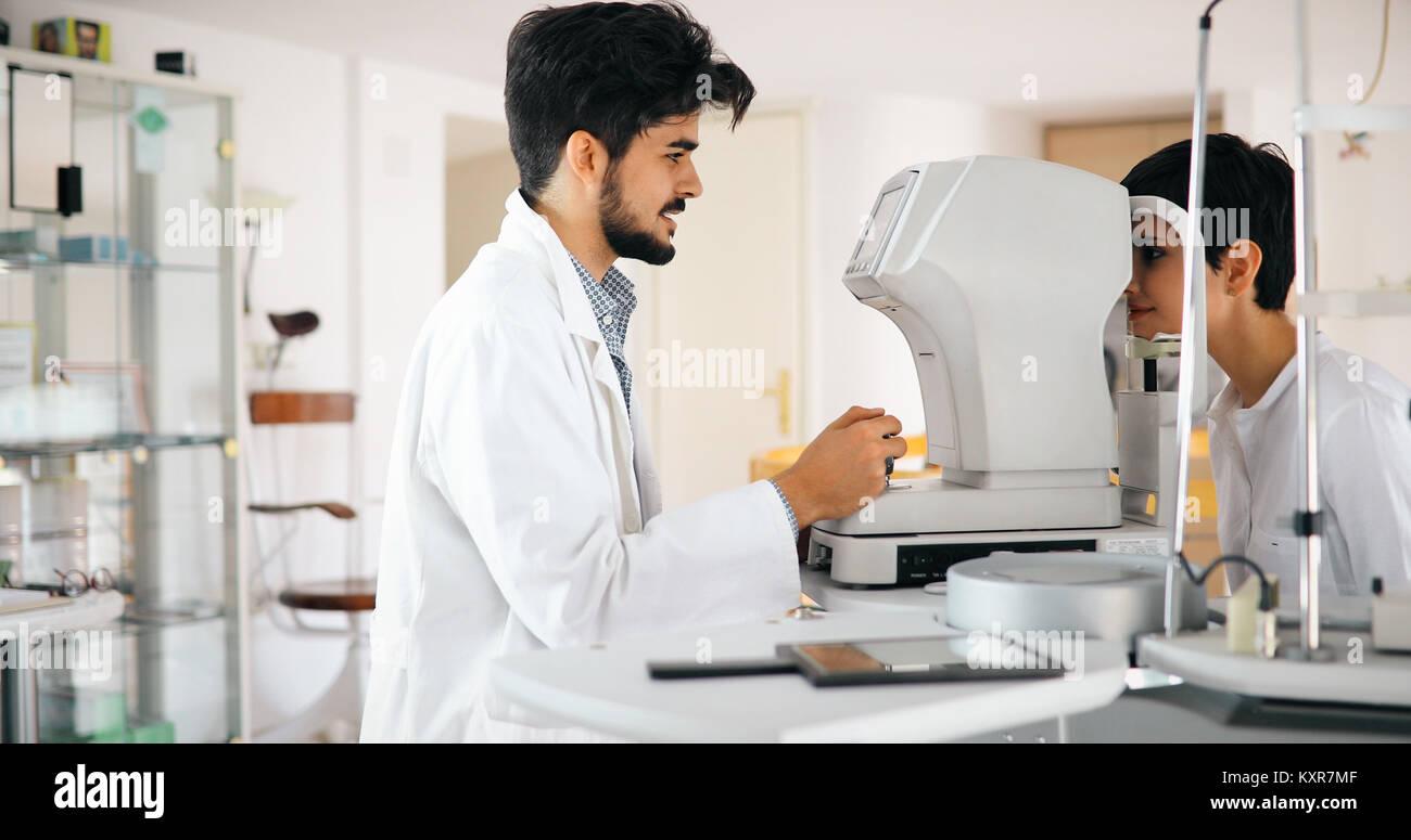 Attentive optometrist examining female patient on slit lamp - Stock Image