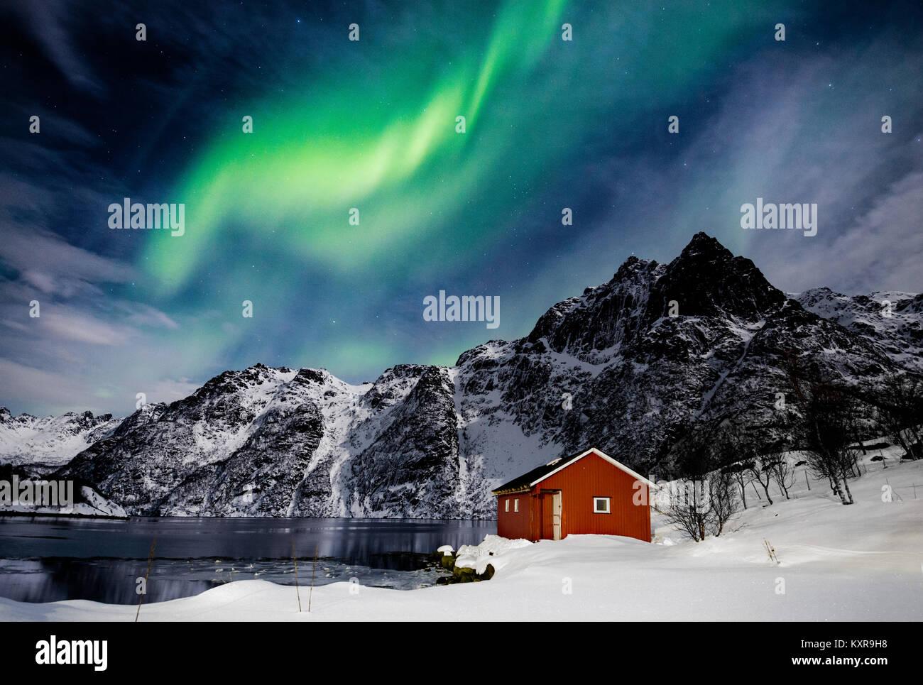 Lofoten, Svolvaer, Aurora Borealis over a frozen lake and red rorbu, Norway. Stock Photo