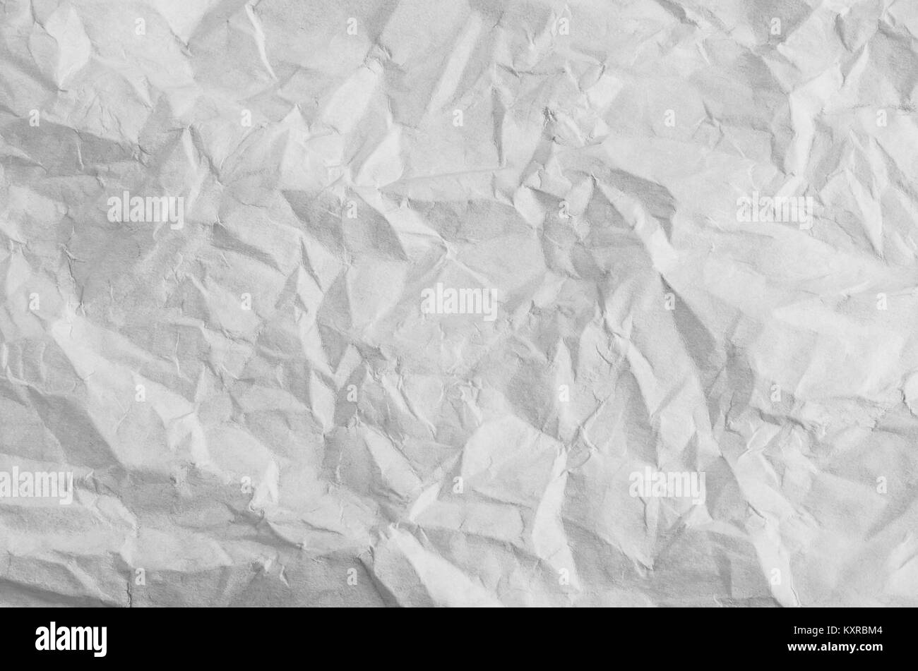 Crumpled, creased and unfolded white paper background texture. - Stock Image