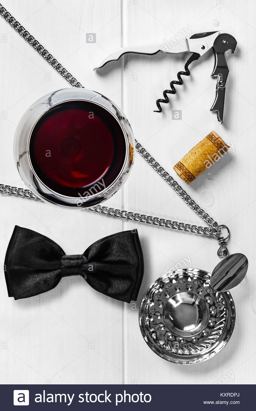 Overhead view of a glass of red wine with a sommelier knife, tastevin, bow tie, and a cork. - Stock Image