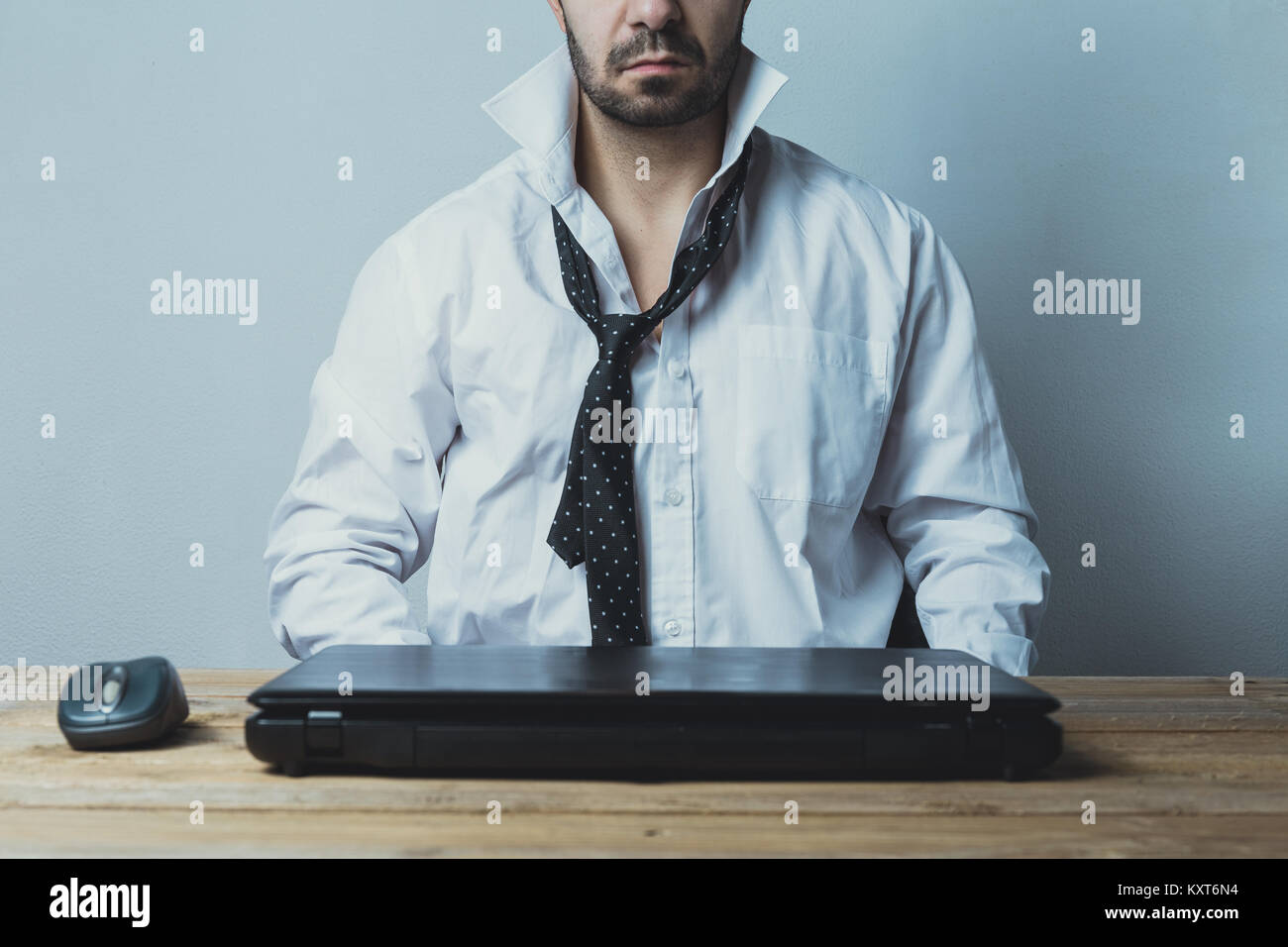 A exhausted young caucasian businessman tired of working. - Stock Image