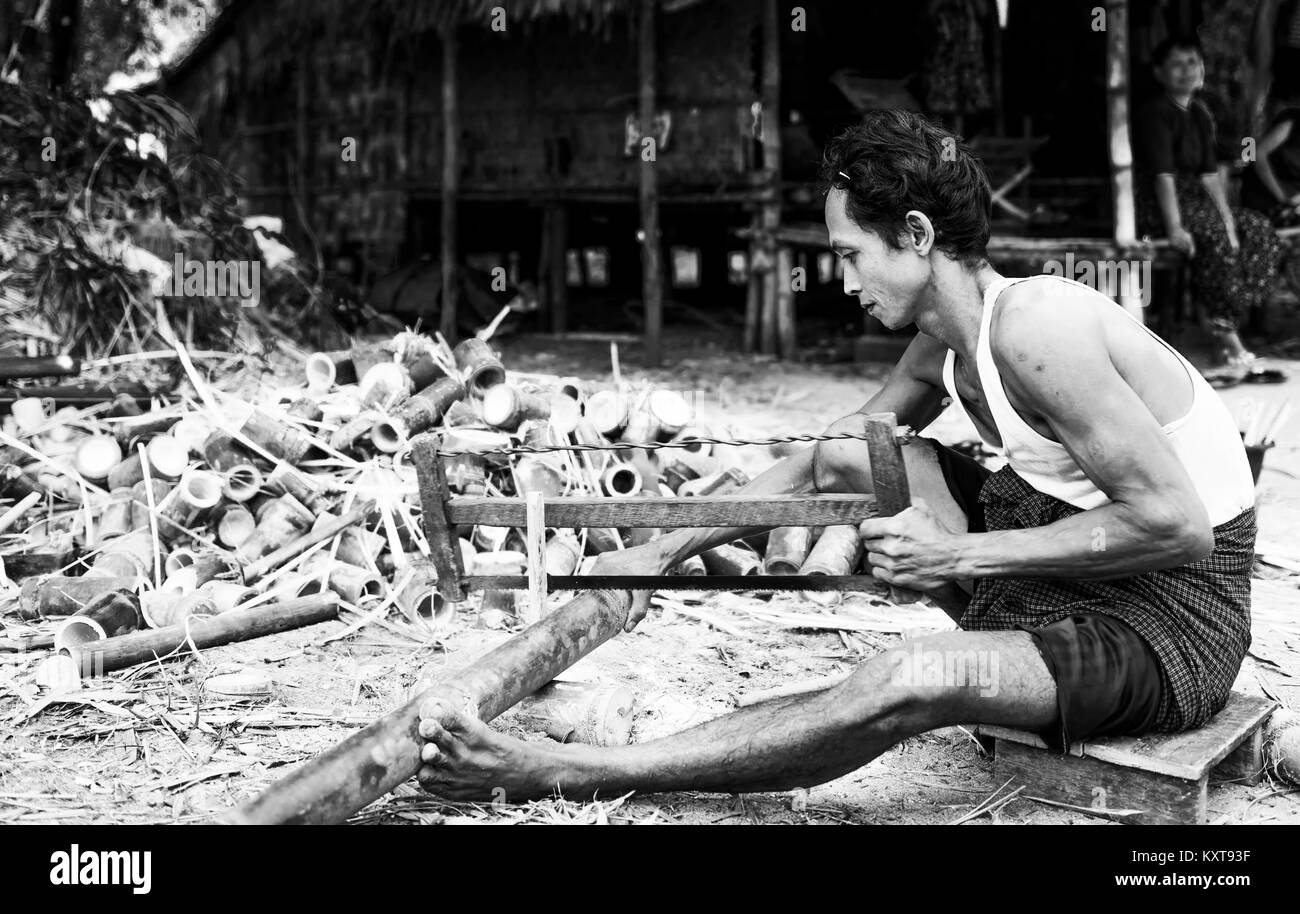 Men cutting bamboo outside his house in Yangon, Myanmar - Stock Image