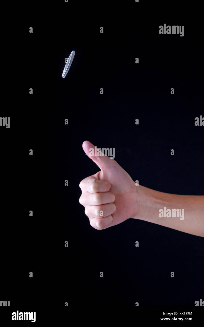 Concept image of flipping a coin up in the air. - Stock Image